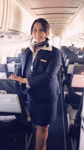 Flight attendant standing inside airplane